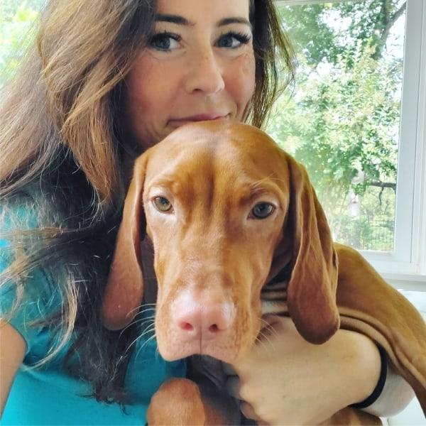 elle smiling with a vizsla puppy